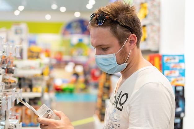 L'homme porte un masque de protection dans le magasin. sécurité, protection de la santé pendant la quarantaine covid-19.