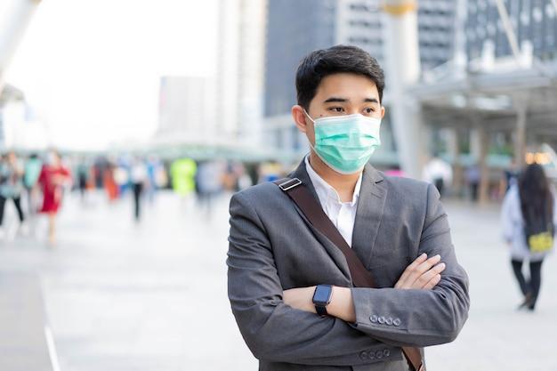 L'homme porte un masque tout en se tenant à l'extérieur du bâtiment avec des gens bondés