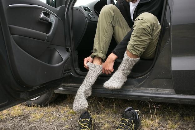 L'homme porte de nouvelles chaussettes sèches fraîches après la randonnée