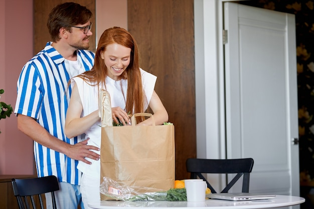 L'homme porte un paquet avec des produits pendant que la femme travaille à la maison