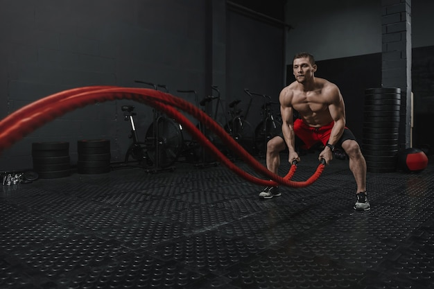 L'homme porte un short rouge faisant des exercices de cordes de combat à la salle de gym crossfit. le concept de sport de motivation. copiez l'espace.