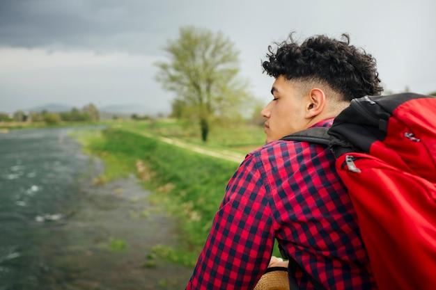 Homme, porter, sac à dos, debout, près, rivière