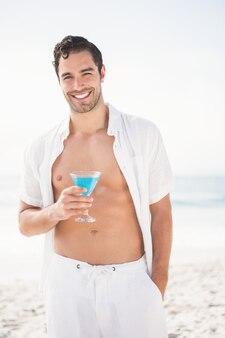 Homme posant et buvant un cocktail