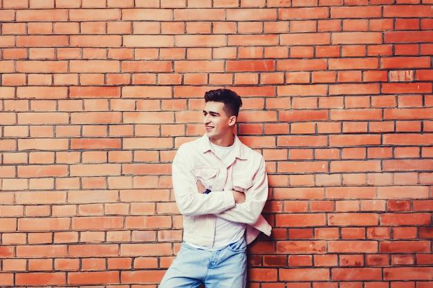 Homme posant contre le mur de briques