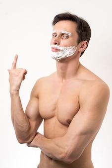 Homme posant avec de la mousse à raser sur le visage
