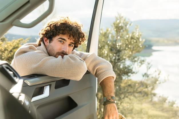 Homme posant avec porte de voiture lors d'un voyage sur la route