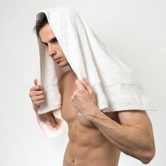 Homme posant avec une serviette de bain sur la tête