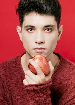 Homme posant en tenant la pomme dans la main