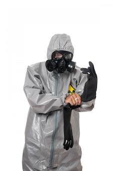Un homme pose dans une combinaison de protection grise, avec un masque à gaz, posant debout