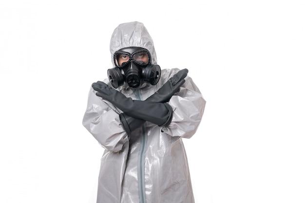 Un homme pose dans une combinaison de protection grise avec un panneau de signalisation jaune, avec un masque à gaz protecteur