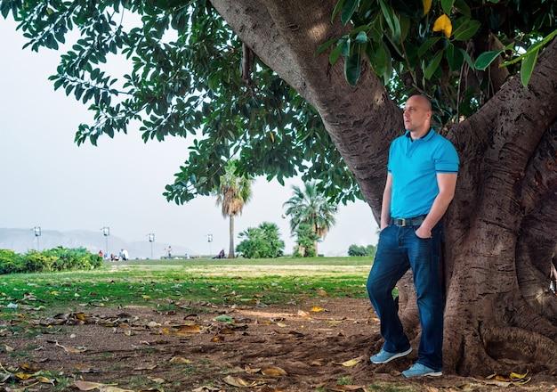 Homme pose à l'extérieur dans le parc