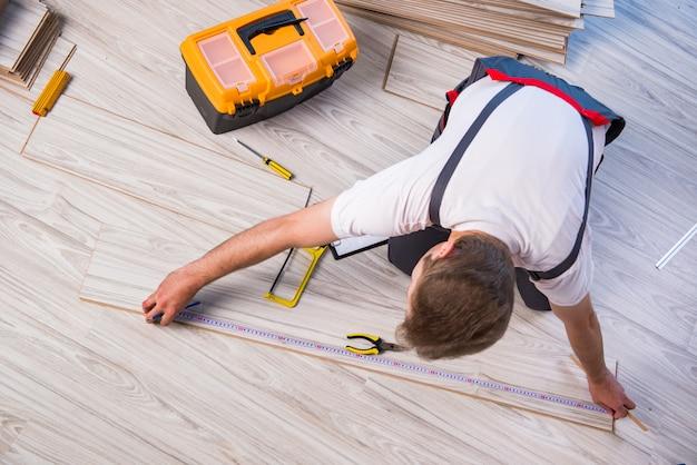 Homme pose de sol stratifié dans le concept de construction