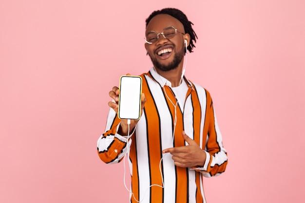 Homme positif joyeux pointant le doigt sur l'écran blanc du smartphone, application publicitaire.