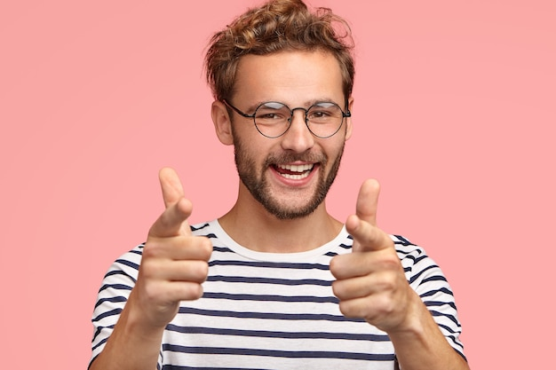 Un homme positif non rasé vous montre une expression heureuse, des cheveux bouclés, des poils, exprime son choix, porte des vêtements rayés, isolés sur un mur rose. l'homme fait le geste du doigt. tu es mon genre