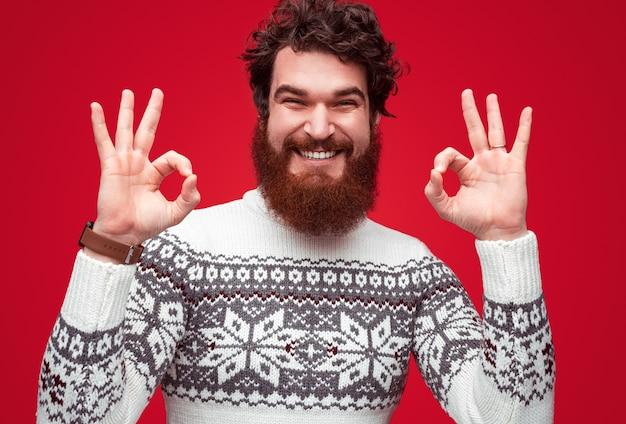 Homme positif en pull d'hiver montrant le signe ok
