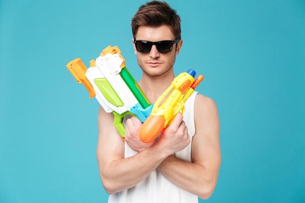 Homme positif à la recherche d'appareil photo et tenant deux pistolets à eau