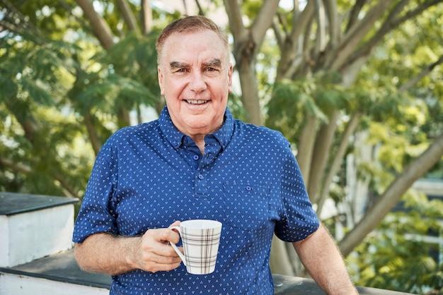 Homme positif avec tasse de thé