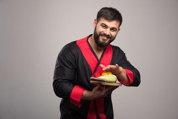 Homme positif tenant une planche de bois avec poivron jaune, courgettes et couteau.