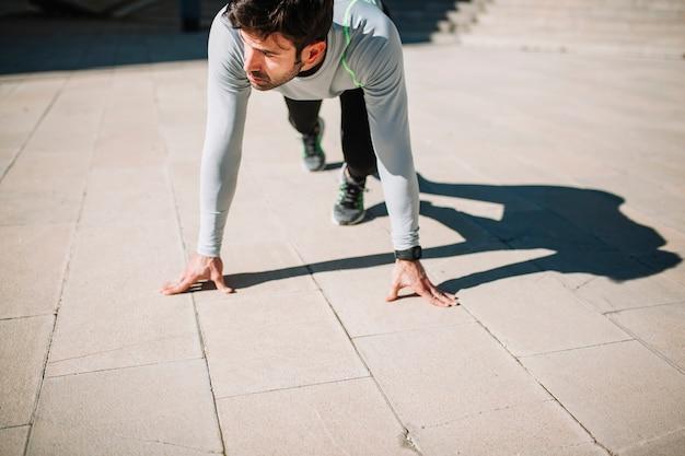 Homme en position accroupie pose sur le trottoir