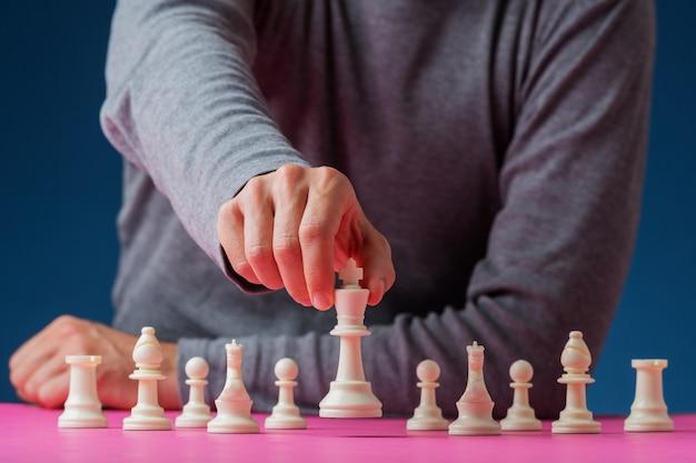 Homme positionnant la pièce d'échecs du roi blanc devant les autres personnages