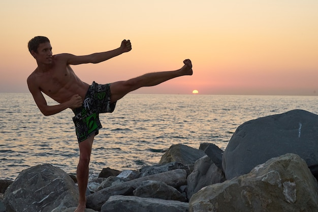 Homme en posture de combat et coucher de soleil sur l'océan. sotchi, russie