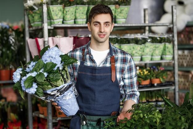 Homme avec un pot de fleurs bleues