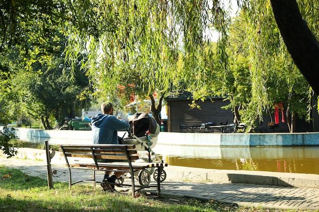 Homme avec poussette assis sur un banc dans le parc de la ville