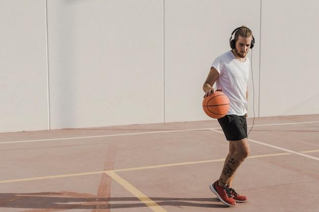 Homme pratiquant le basketball en cour