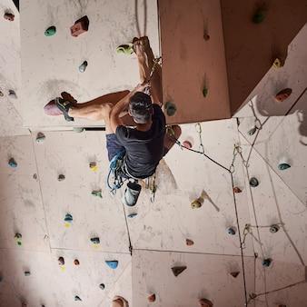 Homme pratiquant l'escalade sur une paroi rocheuse à l'intérieur