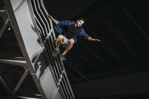 Homme pratiquant le parkour faisant d'énormes sauts effrayants.