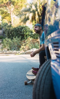 Homme pratiquant avec sa longue planche dans une rue isolée au coucher du soleil