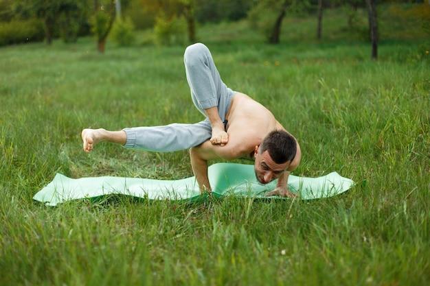 Homme pratiquant le yoga dans le parc.
