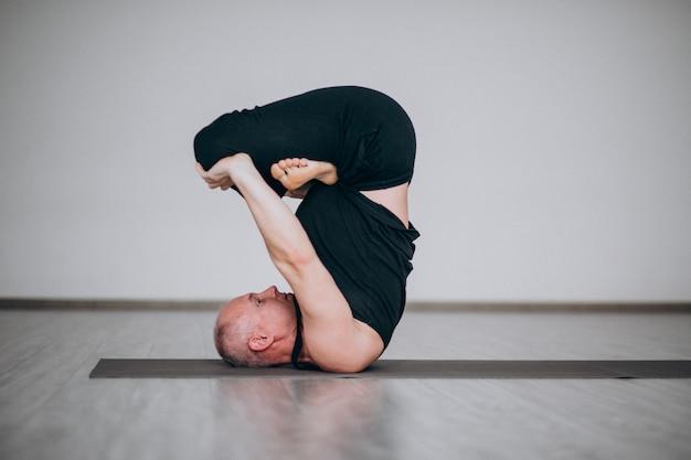 Homme pratiquant le yoga dans la salle de sport