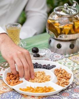 Homme prenant des noix de plaque blanche et avoir un verre de thé aux fruits.