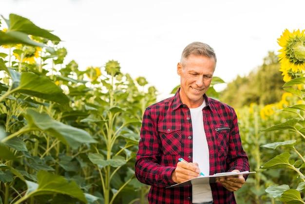 Homme prenant des notes dans un champ de tournesol