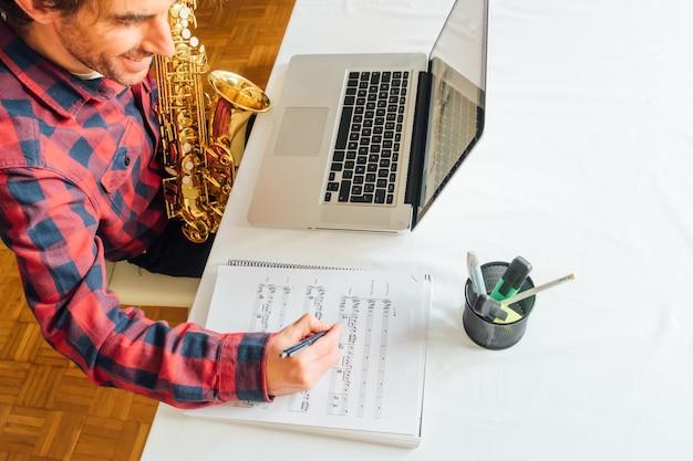 Homme prenant des notes sur des partitions tout en prenant son cours en ligne de saxophone