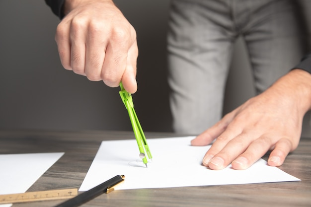 Un homme prenant des notes avec un pied à coulisse sur papier