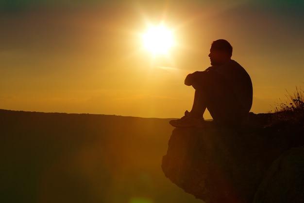 Homme prenant une pause et se détendre dans un pré sous la merveilleuse lumière chaude du coucher de soleil