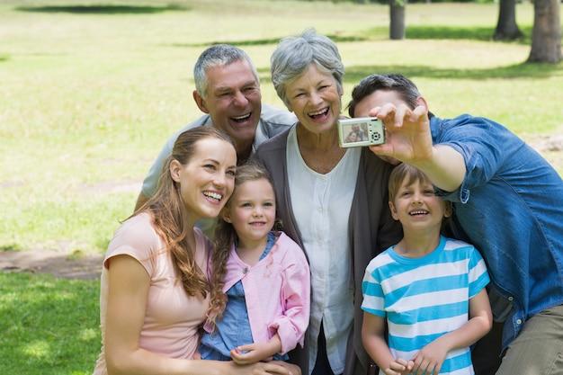 Homme prenant une photo de la famille élargie au parc