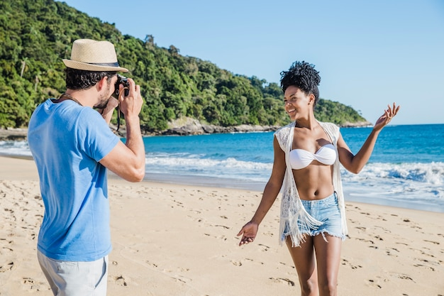 Homme prenant photo de petite amie à la plage