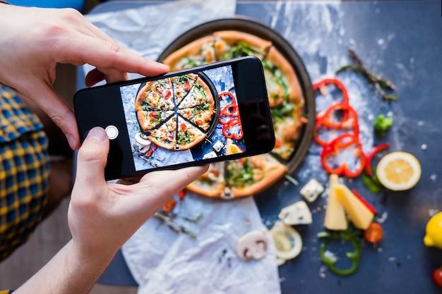 Homme prenant une photo de la pizza avec smartphone vue du processus