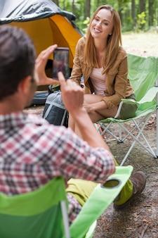 Homme prenant une photo de sa petite amie dans la forêt