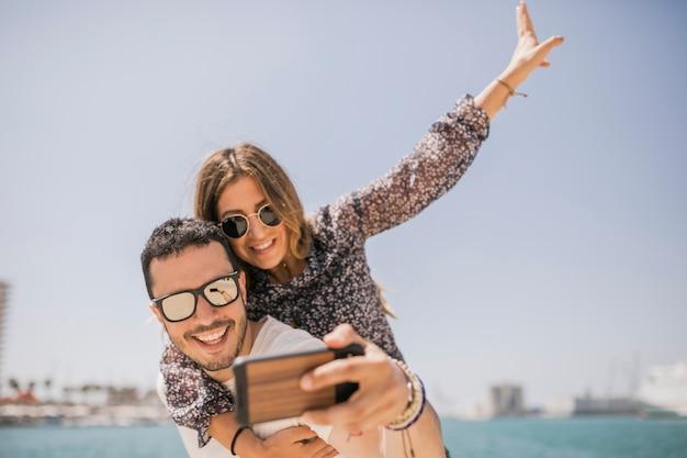 Homme prenant une photo de sa petite amie profitant d'une promenade sur le dos