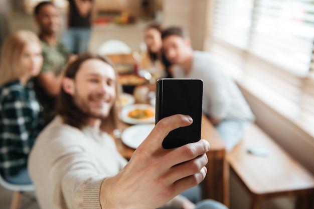 Homme prenant une photo de selfie avec des amis dans la cuisine