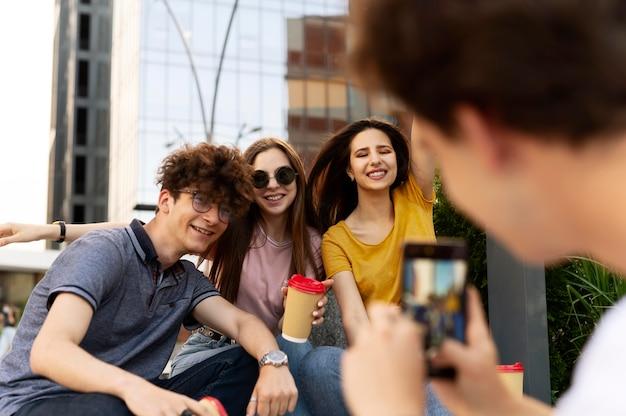 Homme prenant une photo de ses amis à l'extérieur