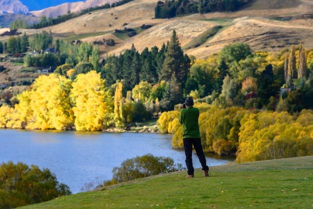 Homme prenant des photos de beaux paysages autour du lac mapourika, côte ouest de la nouvelle-zélande