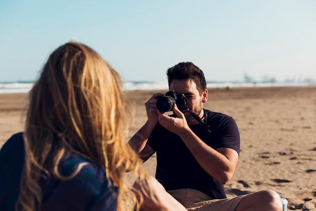 Homme prenant des photos de petite amie sur la plage