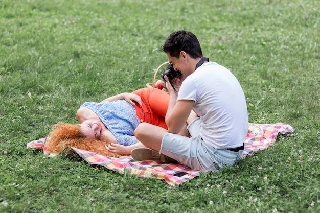 Homme prenant des photos de sa petite amie sur l'herbe