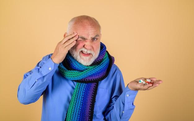 Homme prenant des pilules migraine maux de gorge traitement médicament pharmaceutique douleur vieil homme toucher