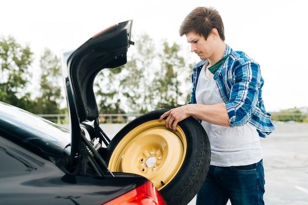 Homme prenant un pneu de secours